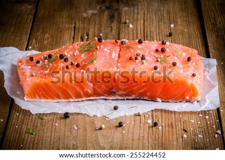 piece of fresh salmon with pepper and sea salt on wooden rustic background - stock photo