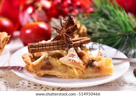 piece of homemade apple pie with raisins,cinnamon and anise star on white plate for christmas time