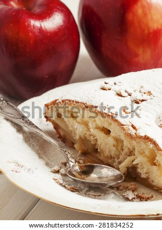 Piece of homemade apple sponge cake on a plate and fresh apples, selective focus