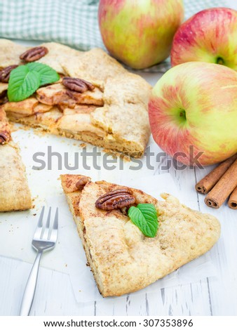 Piece of homemade fresh apple galette with pecan nuts - stock photo