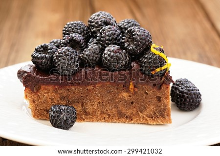 Piece of homemade yummy chocolate pie with ganache, fresh blackberries and lemon peel decorated with icing sugar in white plate on wooden table - stock photo