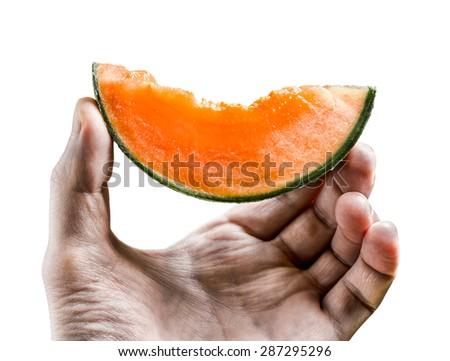 piece of juicy orange melon holds men's hand isolated on white background - stock photo