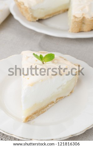 piece of lemon tart with meringue decorated with mint - stock photo
