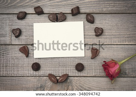 Piece of paper, chocolates and a single rose - stock photo