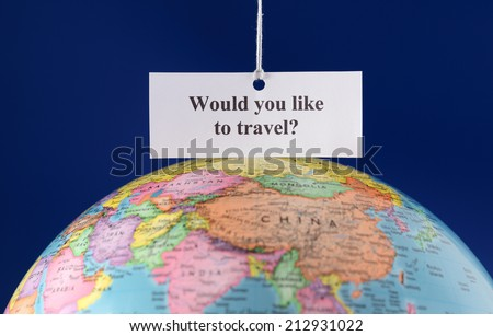 """Piece of paper with text """"Would you like to travel?"""" over globe.  - stock photo"""