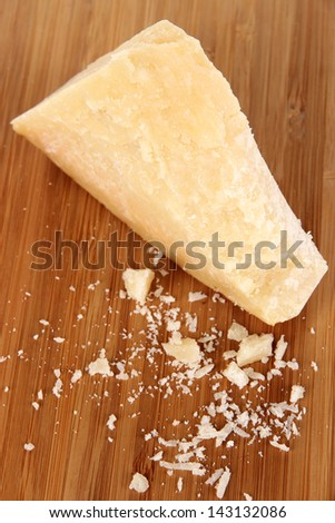 Piece of Parmesan cheese on wooden board close-up - stock photo