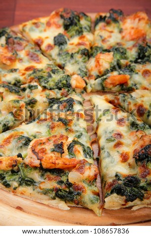 Piece of pizza on wood with prawn and spinash. - stock photo