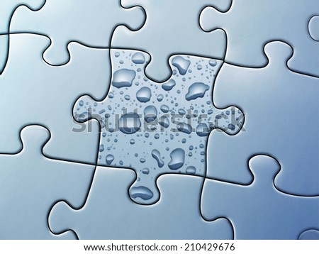 Piece of puzzle with drops of water - stock photo
