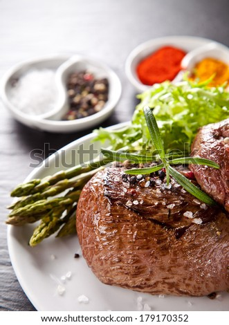 Piece of red meat steak with rosemary served on black stone surface. - stock photo