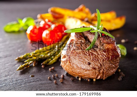 Piece of red meat steak with vegetable and herbs, served on black stone surface. - stock photo