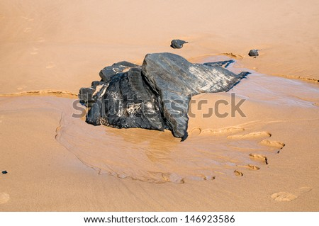 Piece of slate laying on a Portuguese beach in a little water stream. This type of stone is used as construction material