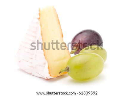 Piece of soft cheese and grapes. Isolated on a white background.