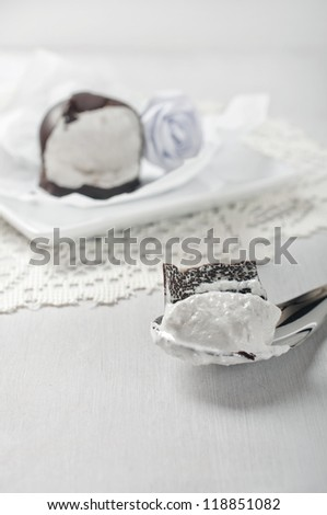 Piece of soft marshmallow in chocolate on a spoon and half marshmallow on a plate. Shot in high key technique. - stock photo