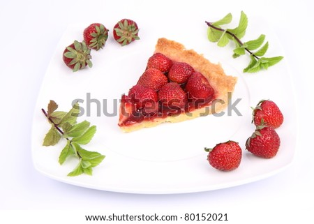 Piece of Strawberry Tart on white plate decorated with strawberries and mint twigs