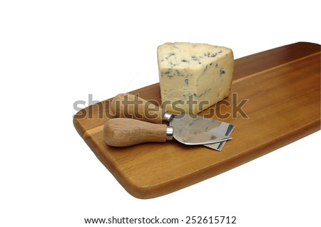 Piece of the blue mold cheese and two special cheese knifes on the brown cutting board isolated over white - stock photo