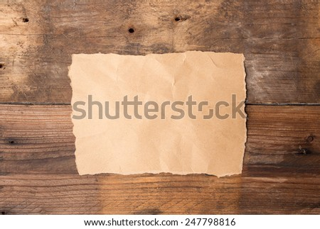 Piece of torn paper on old grunge wooden table - stock photo