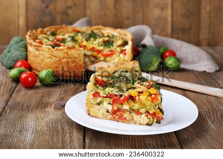 Piece of Vegetable pie with broccoli, peas, tomatoes and cheese on plate, on wooden background - stock photo