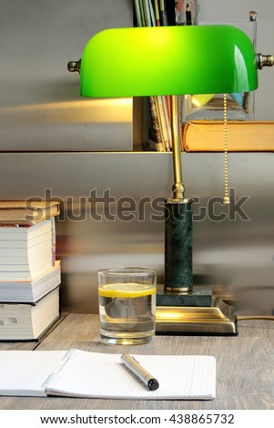 Piece of work place (interior) with green lamp, wooden table, books, notebook paper, pen and a glass with water and lemon slice