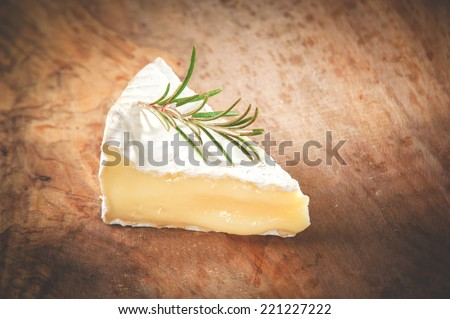 Piece smelly camembert cheese on a wooden rustic table  - stock photo