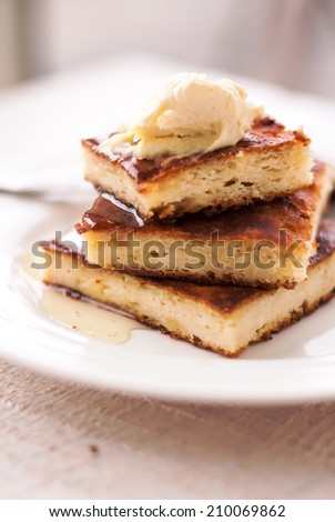 pieces cottage cheese casserole on a round plate and a cream, pour honey  - stock photo