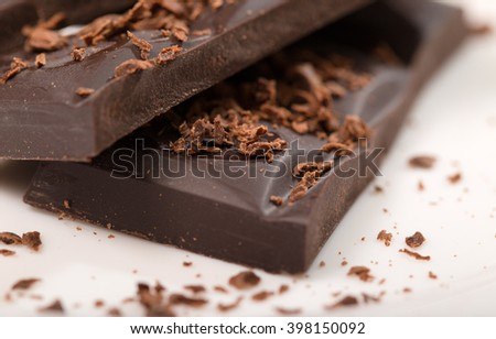 Pieces from a chocolate bar and chocolate crumbs on a white background. Close up, small depth of sharpness - stock photo
