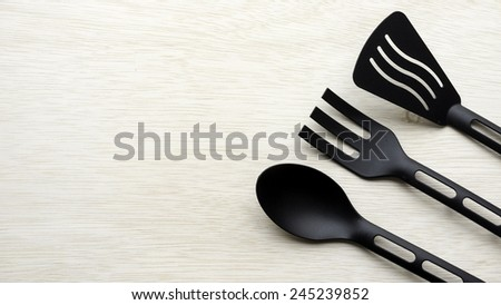 Pieces of black kitchen utensil set that looks like fork and spoon for pots and pans with non-stick coating on wooden table surface with some room for text. - stock photo