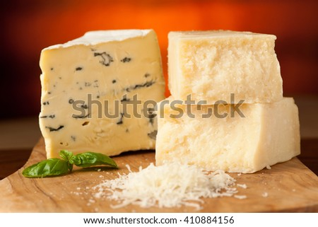 pieces of blue cheese and parmesan on a wooden cutting board being cutt with cheese knife with spices  on a wooden restaurant table in background - stock photo