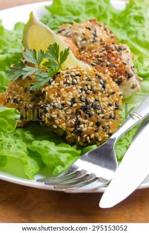 pieces of chicken in sesame on lettuce leaves - stock photo