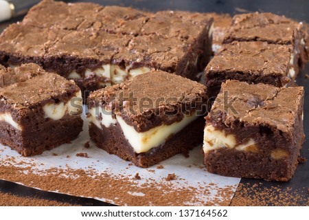 Pieces of chocolate cheesecake brownies on a baking paper - stock photo