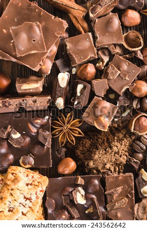 Pieces of chocolate, cookies, nuts on a wooden background - stock photo