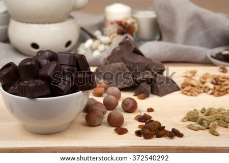 Pieces of chocolate, raisins, dates, cane sugar, nuts and spice on a wooden board. - stock photo
