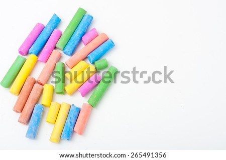pieces of color chalk scattered on white backgrond, horizontal image with room for text - stock photo