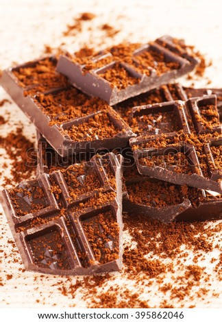 Pieces of dark chocolate on a wooden table with cacao powder, closeup shot, selective focus, vertical - stock photo