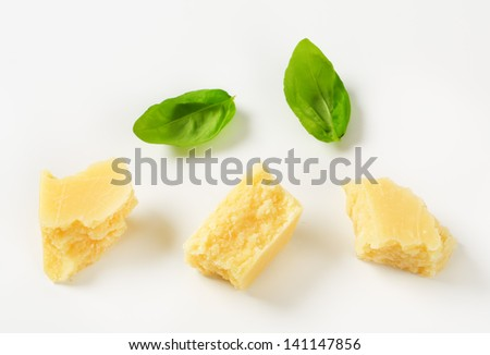 Pieces of delicious parmesan cheese on a white background - stock photo