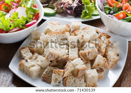 Pieces of fresh bread and salad setting on table.