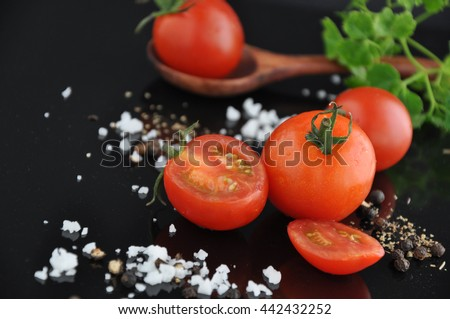 Pieces of fresh cherry tomato with salt and black pepper on black background - stock photo