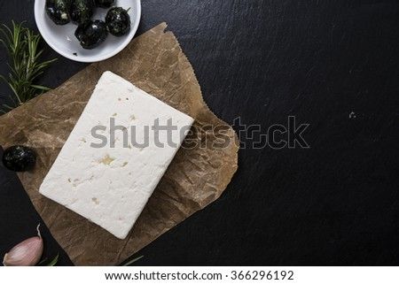 Pieces of fresh cutted  feta cheese (on a vintage slate slab) - stock photo