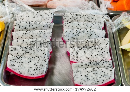 Pieces of fresh dragon fruit prepare to eat on market stand. - stock photo