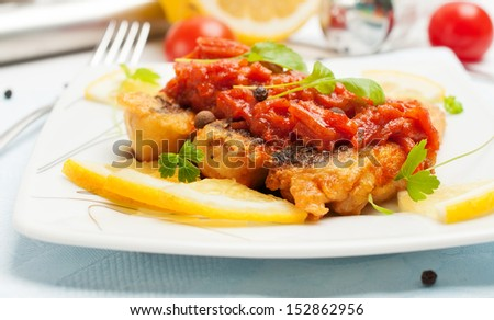 Pieces of fried fish in tomato sauce with carrots. Closeup photo. - stock photo