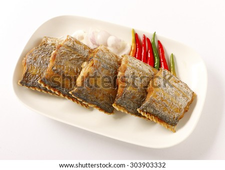Pieces of fried fish on a white plate on white background