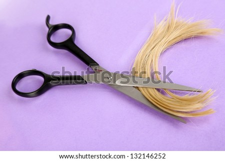 Pieces of hair cut with scissors on purple background
