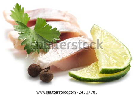 Pieces of herring with lime, pepper and parsley isolated on a white background.