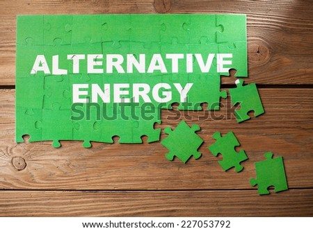 Pieces of jigsaw puzzle on a wooden board with a word ALTERNATIVE ENERGY written on them. - stock photo