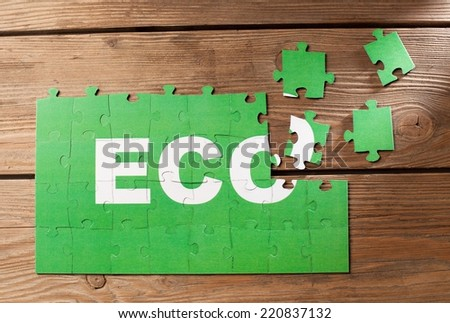 Pieces of jigsaw puzzle on a wooden board with a word ECO written on them.