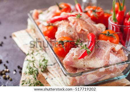 pieces of meat of chicken with tomatoes and pepper in a bowl on a table, selective focus, copy space