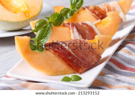 pieces of melon wrapped in ham with basil on a white plate on the table. Horizontal close-up  - stock photo