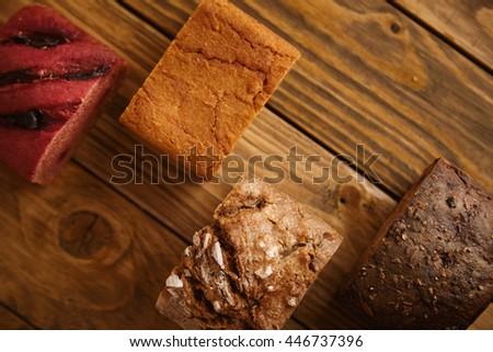 Pieces of mixed homemade breads presented in different levels on wooden table as samples for sale: , sweet potato, sea salt, rye and beetroot. Close up - stock photo