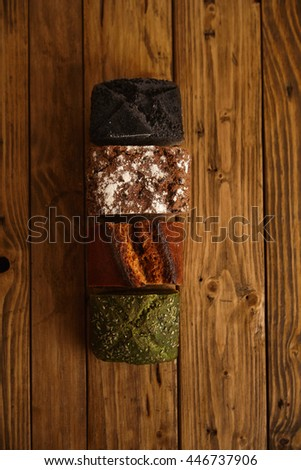 Pieces of mixed homemade breads presented on rustic table as samples for sale: pistachio, dry tomato, rye and coal. All healthy artisan made - stock photo