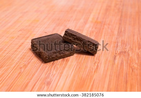 Pieces of Moroccan hashish laid on the wooden desk - stock photo