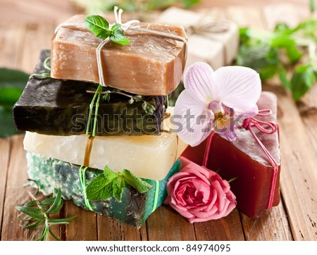 Pieces of natural soap with herbs and flowers. - stock photo
